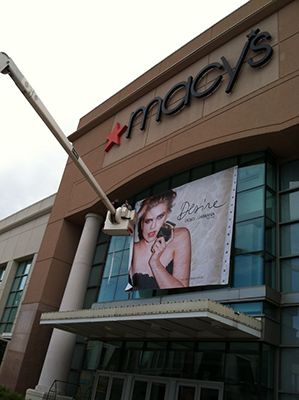 bucket lift being used to hand a department store window banner at Macys